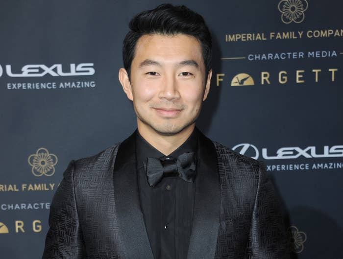Simu wears a black suit and black shirt and bow tie