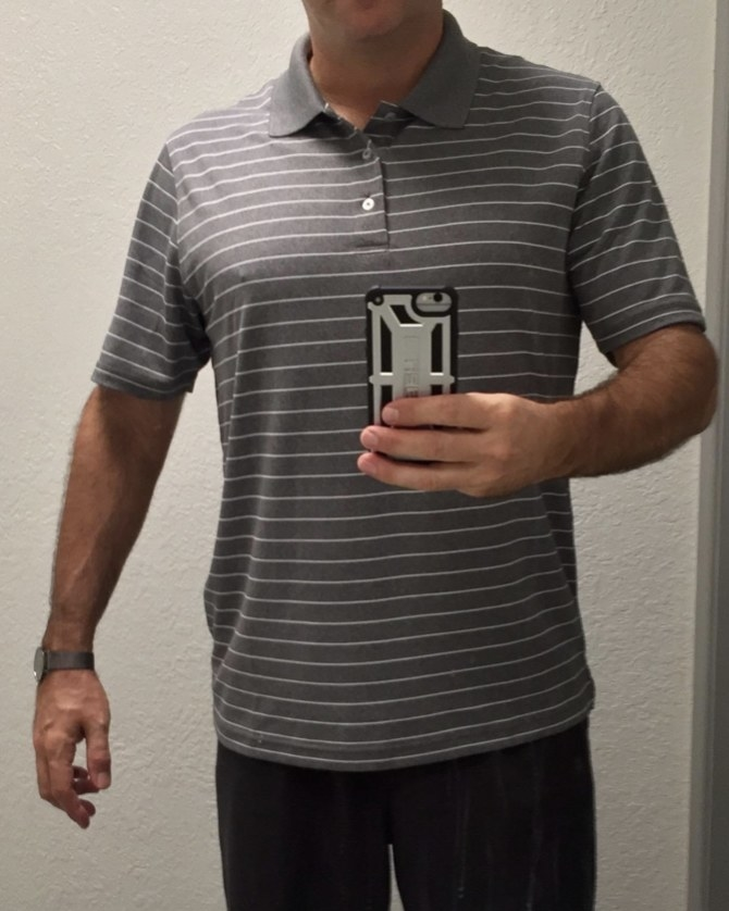 A reviewer wearing a grey and white striped polo shirt