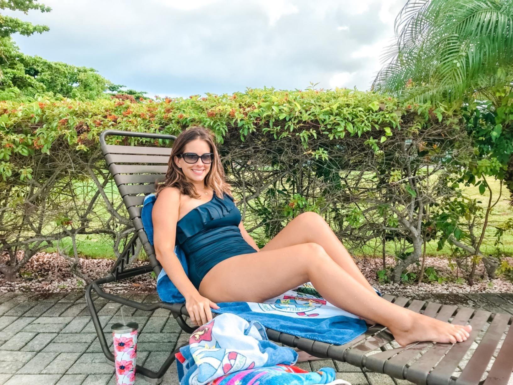 Reviewer wearing turquoise bathing suit with side ruching