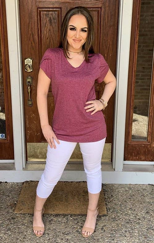 A reviewer modeling a pink v neck tshirt
