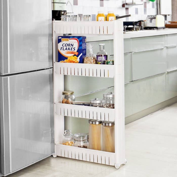A slim storage rack with jars on it being wheeled into the space between a fridge and counters