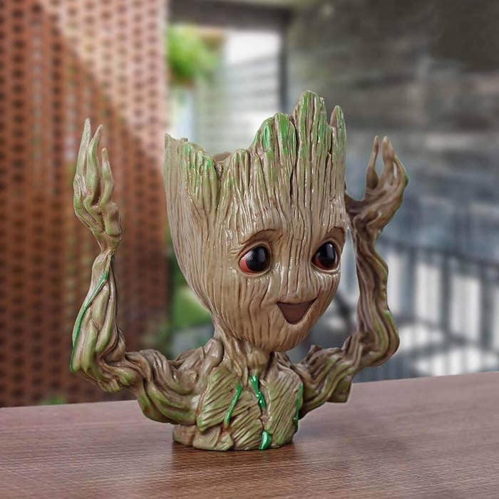 A Groot flower pot holding its arms up
