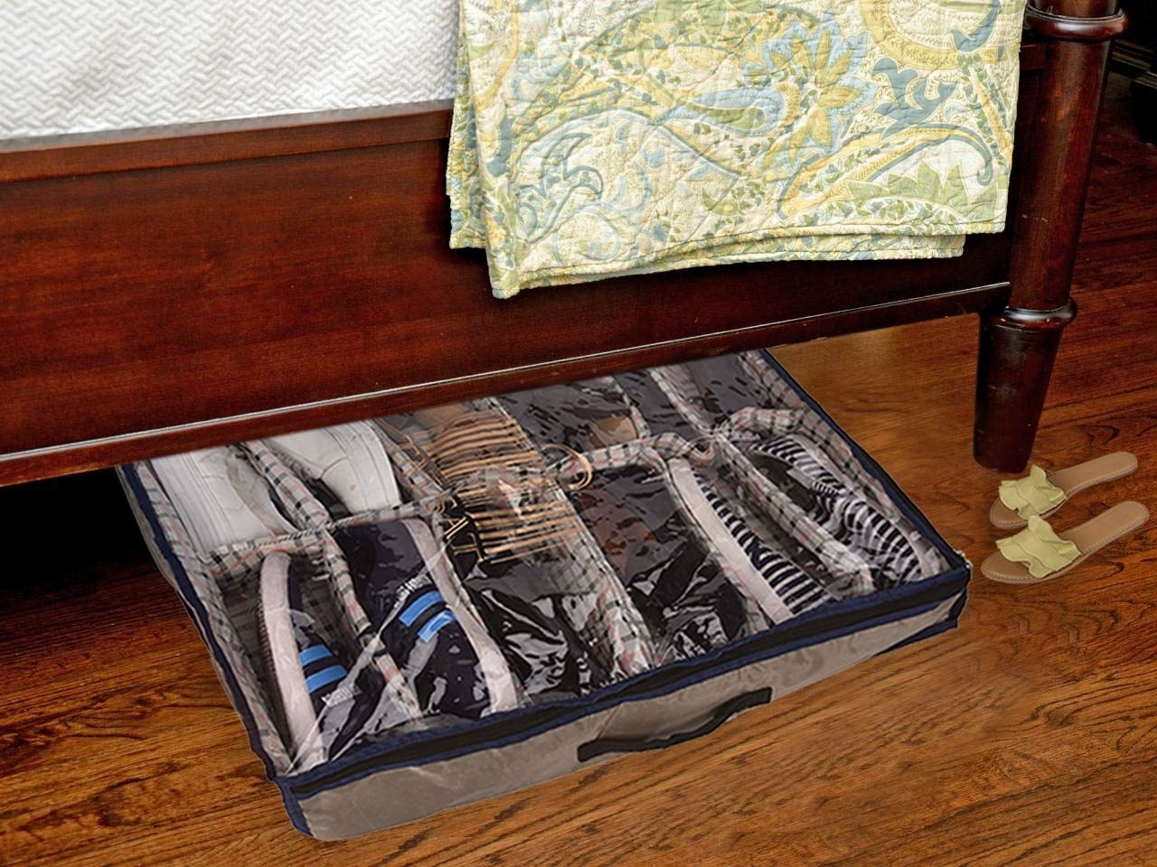 An under-bed shoe organiser with shoes in it under a bed