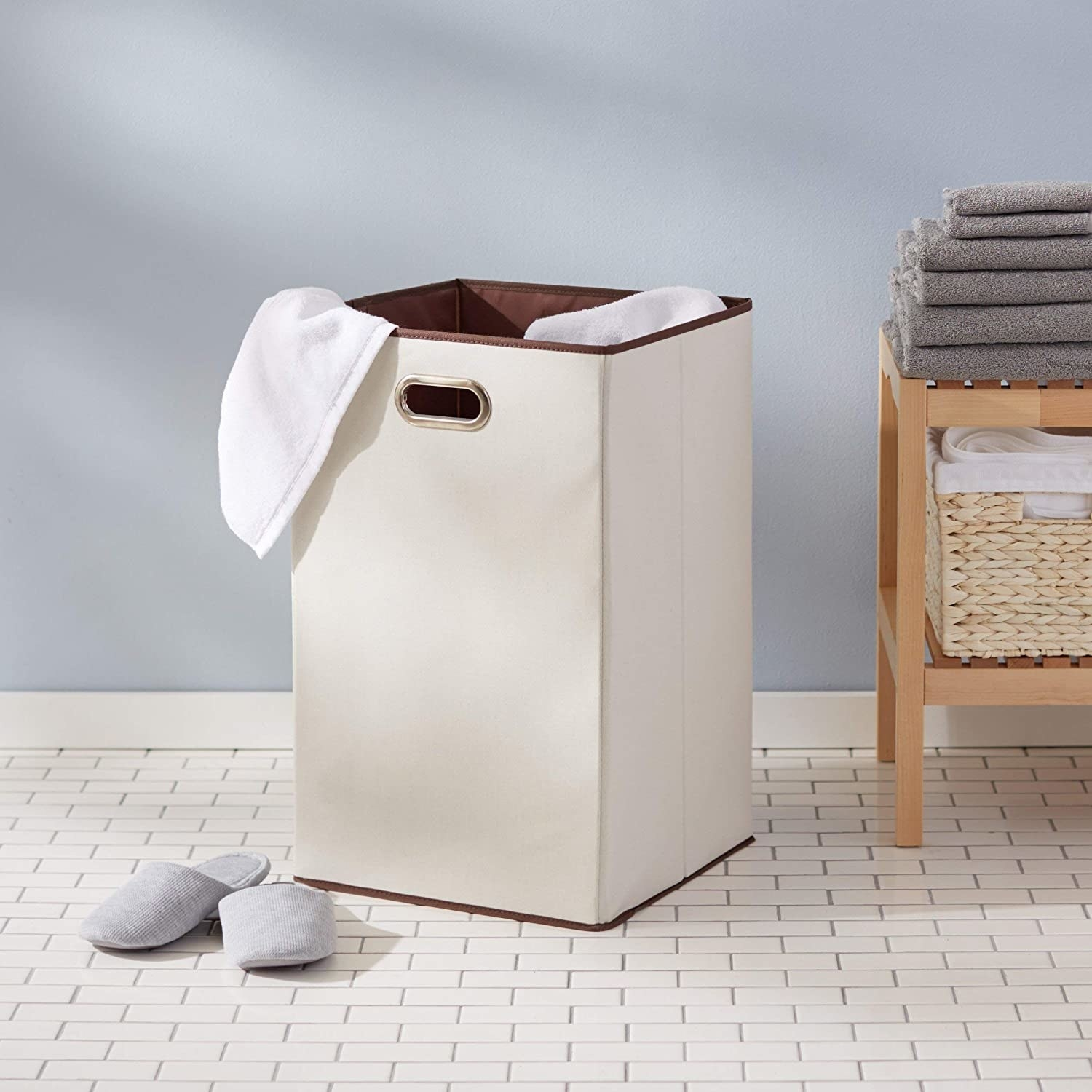 A foldable laundry hamper with a towel in it next to a pair of shoes and a wicker basket