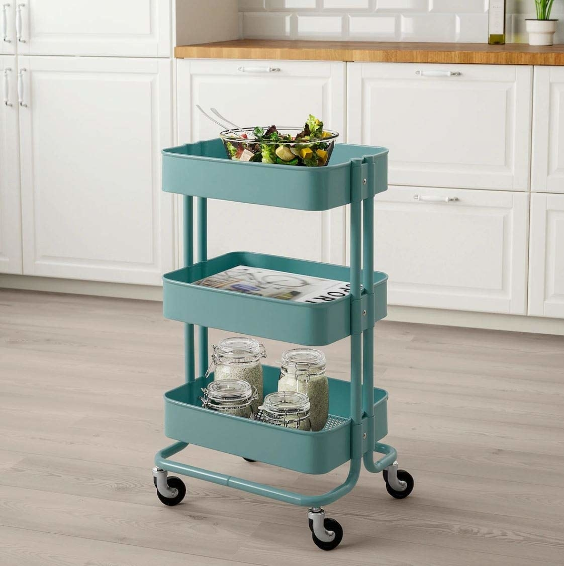A blue Ikea utility cart with jars on it