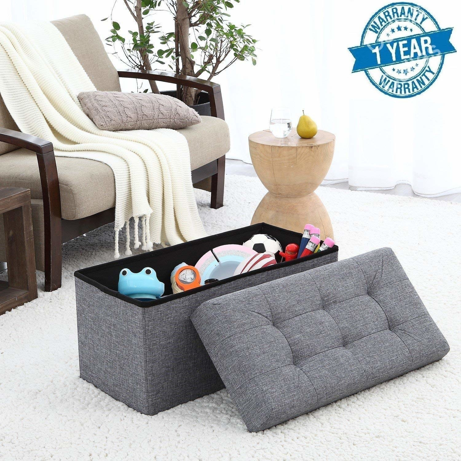 A grey storage ottoman on the floor with toys in it next to a sofa with a blanket on it