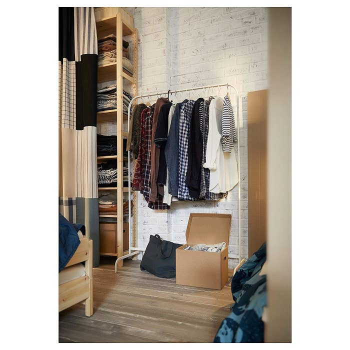 A white wall rack with clothes on it next to storage boxes