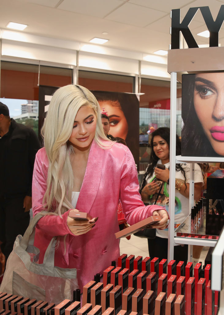Kylie looking at a display of her makeup products at a store