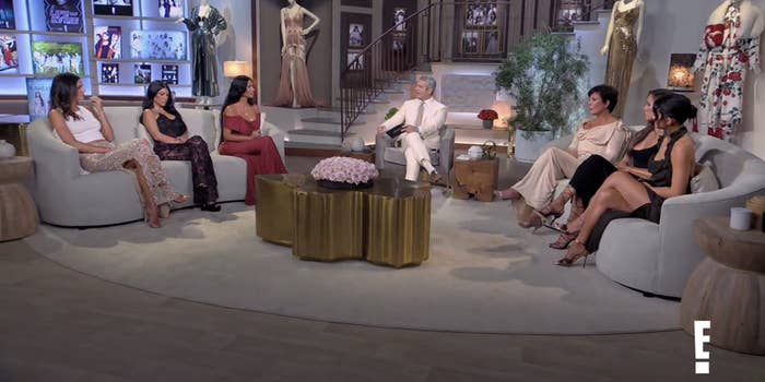Shot of the Kardashians and Jenners sitting on either side of Andy Cohen