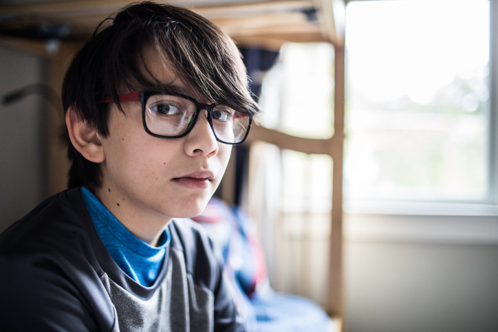 Young person wearing large, plastic-frame eyeglasses