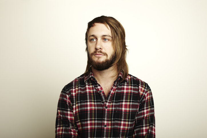 Person with a beard wearing a flannel shirt