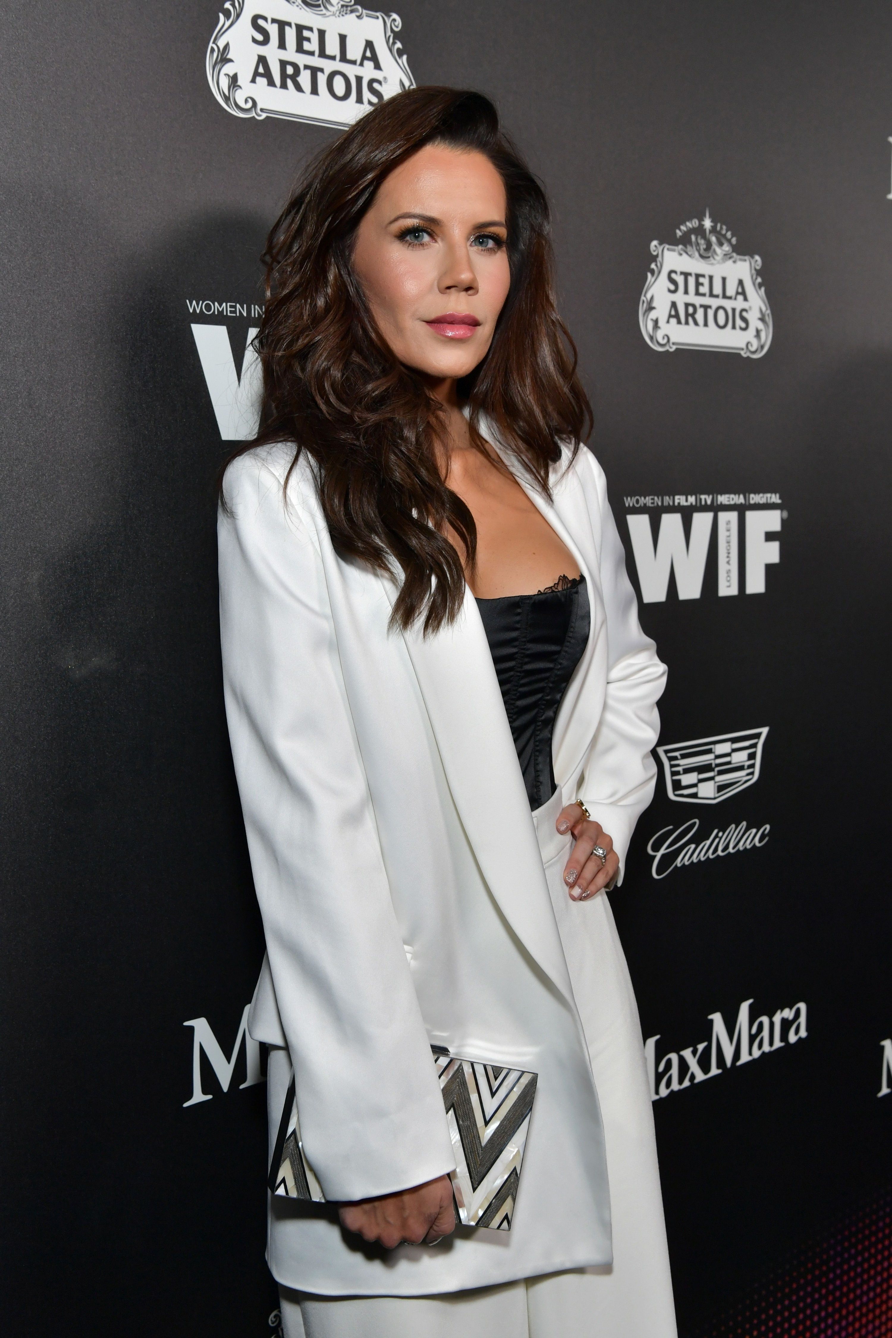 Tati, hand on hip, in a white suit on the red carpet