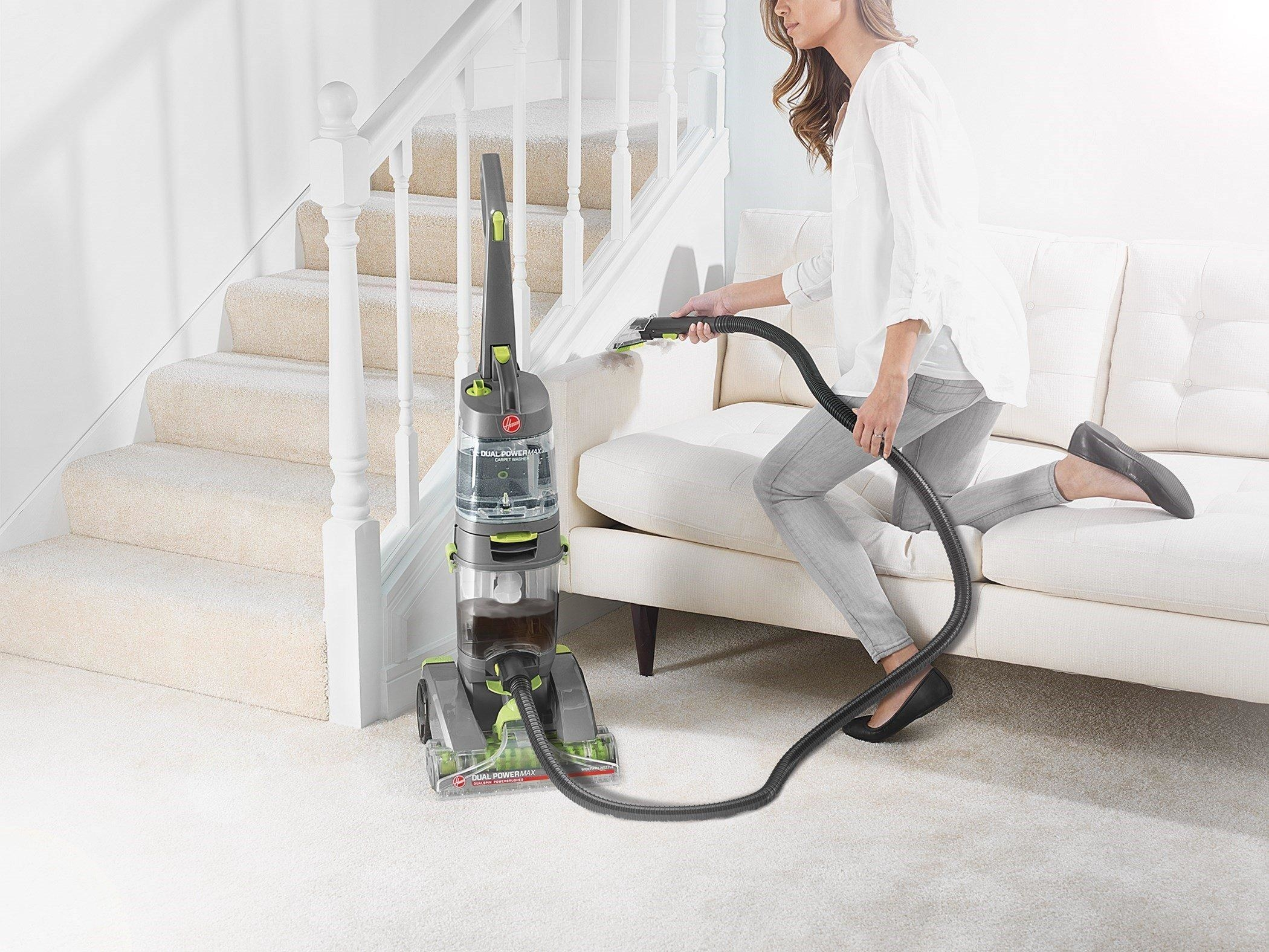 Model using grey and green vacuum in living room