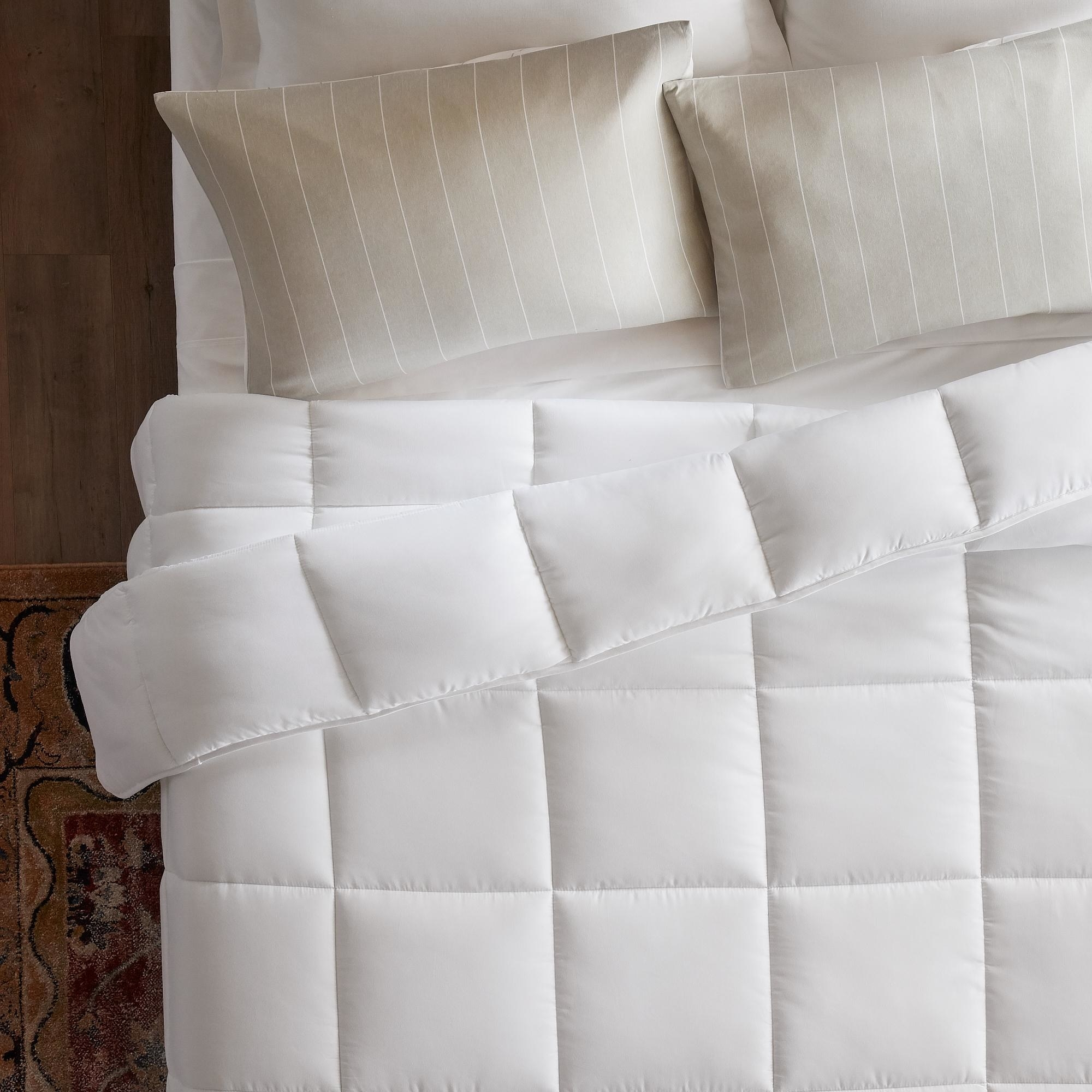 A white comforter on a bed