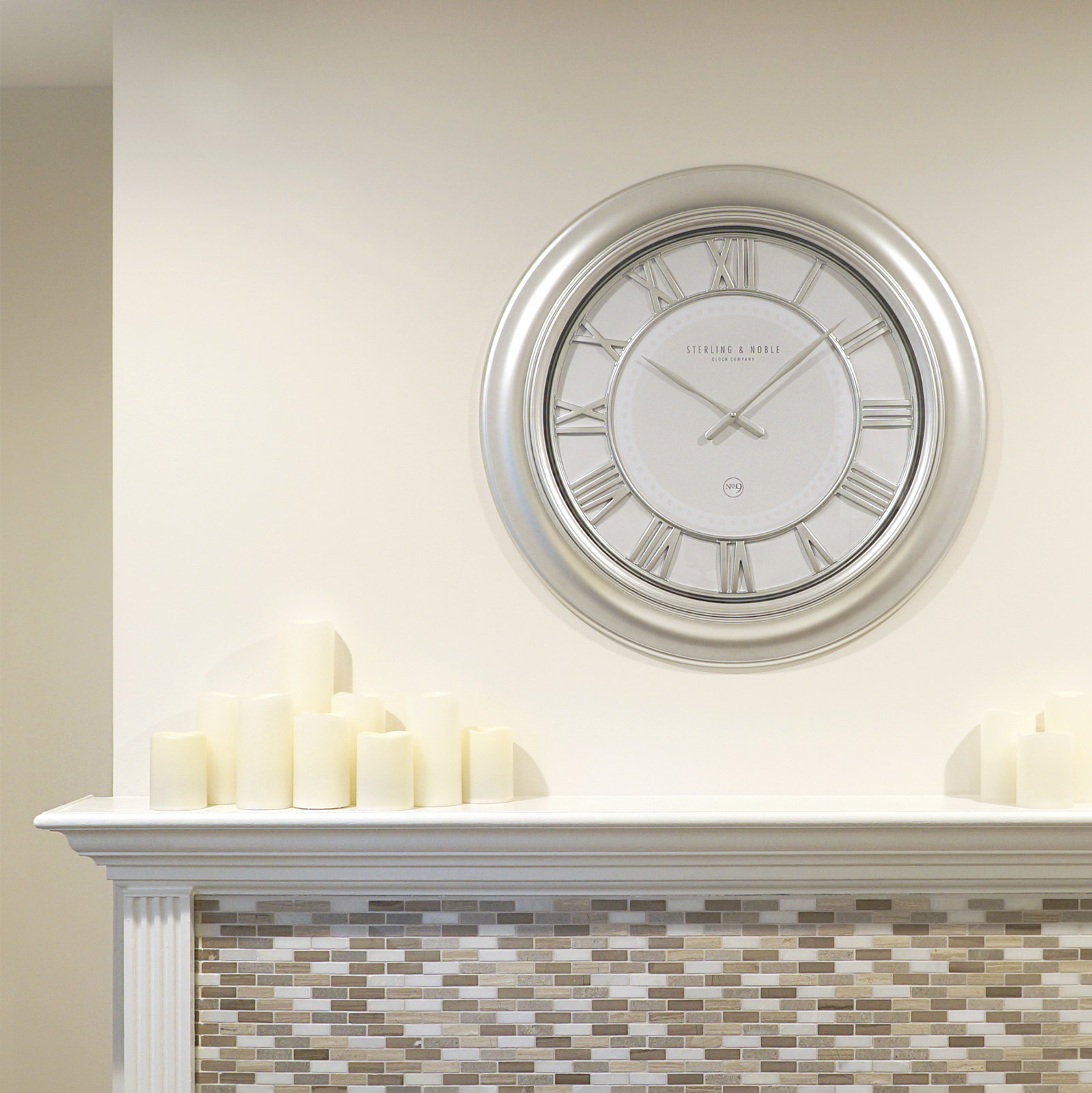 A white and silver clock hung up on a wall