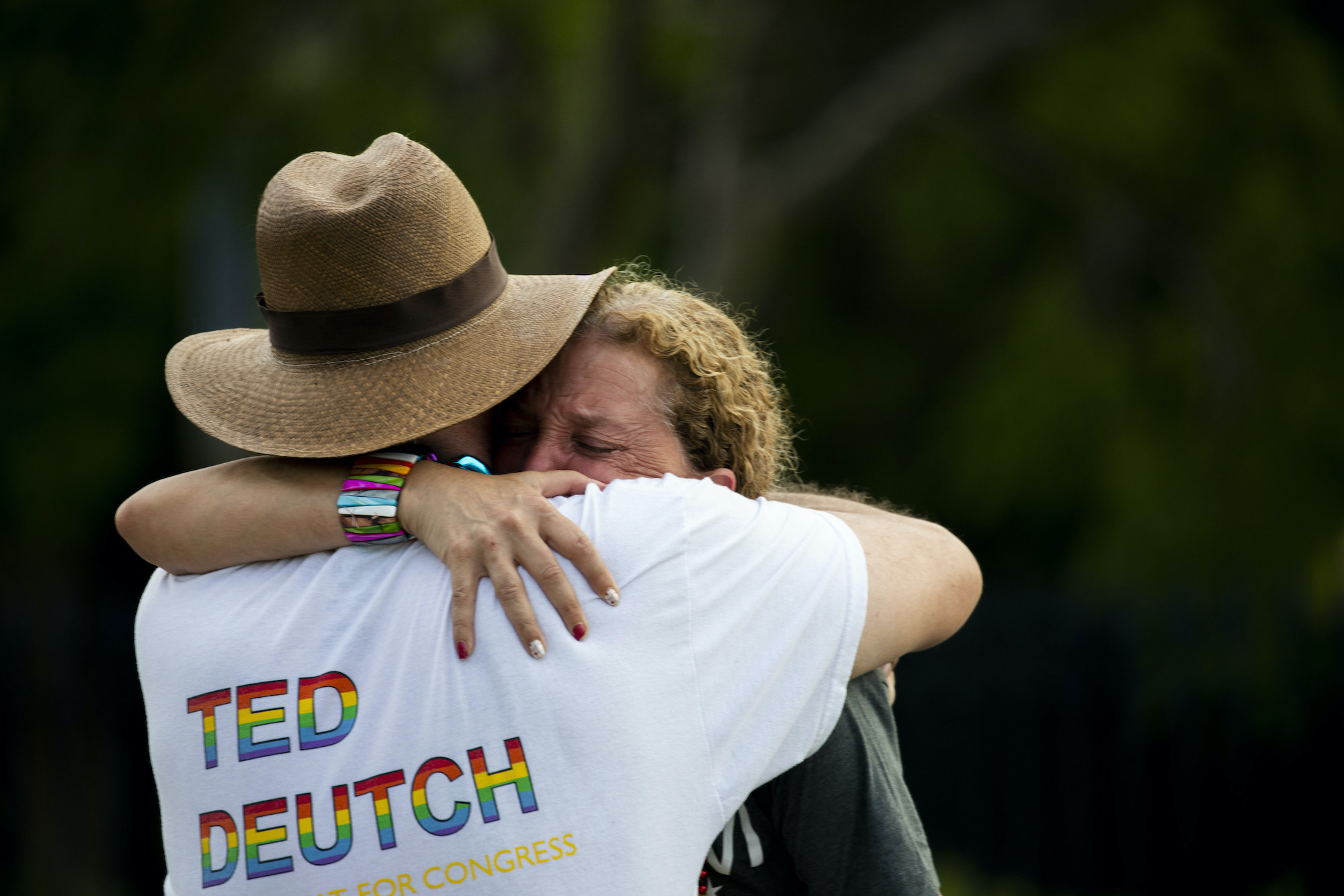 Debbie Wasserman Schultz is crying as she is hugged by another person