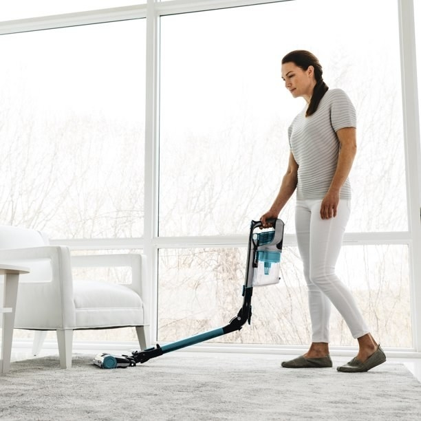 A model vacuums with the stick part bent in half to get under a chair
