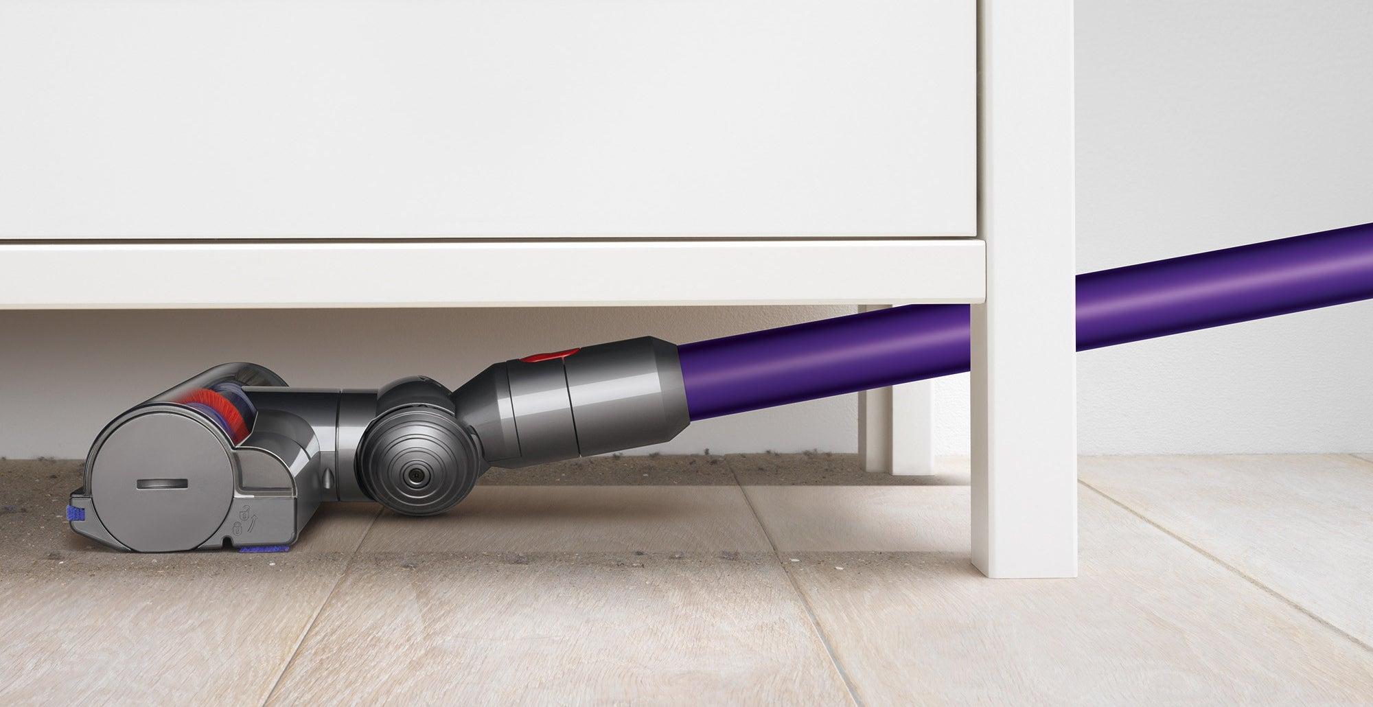 The vacuum reaches under a dresser
