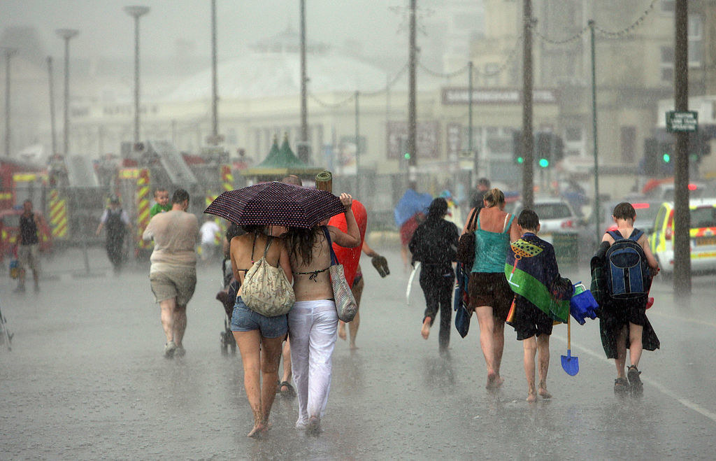 People in England walking on the sidewalk while it's raining