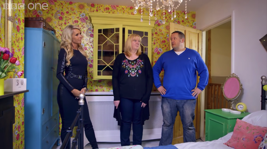 Two contestants and a host standing in a bedroom that has been decorated on a reality TV show