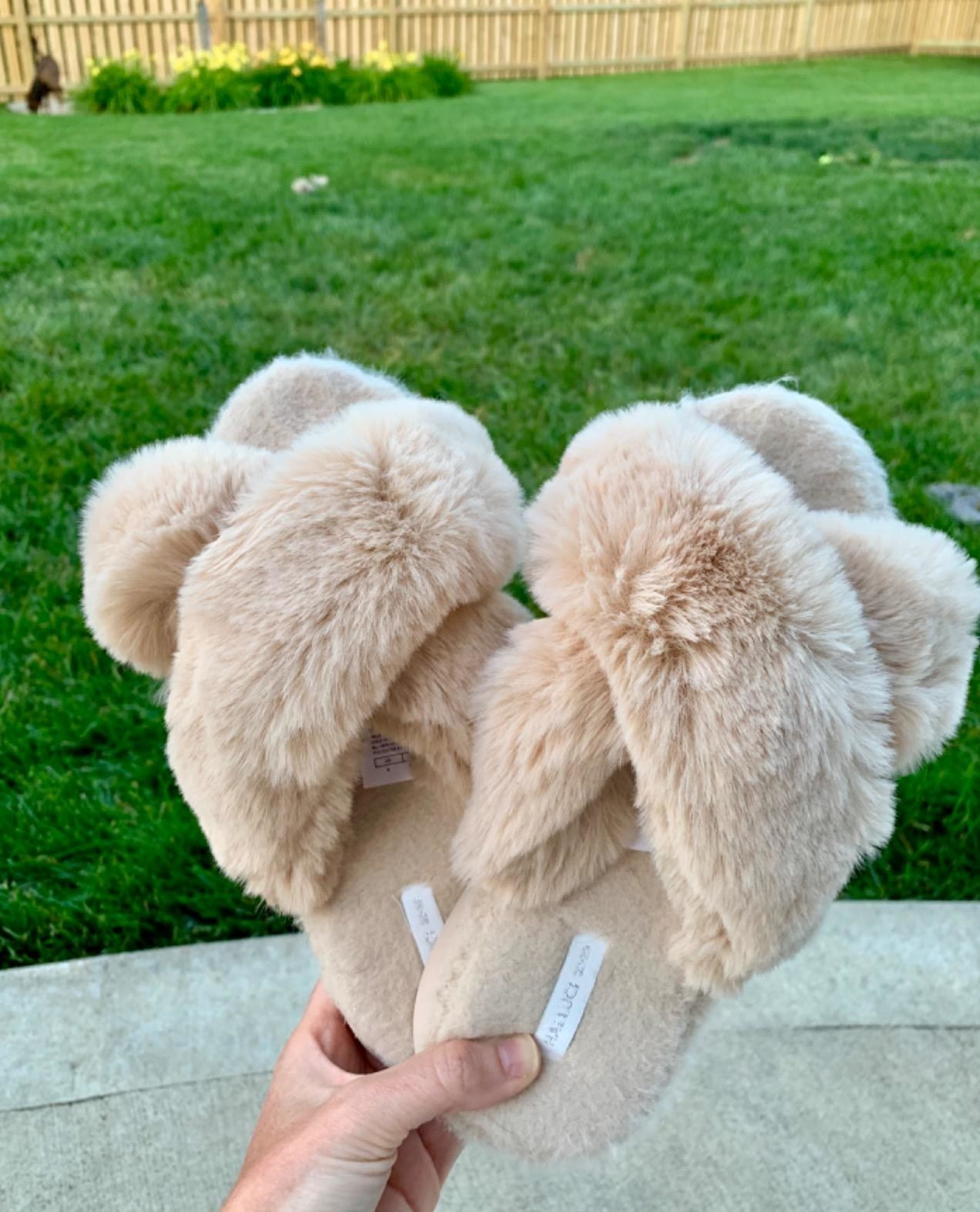 Reviewer holding the beige criss-cross slippers