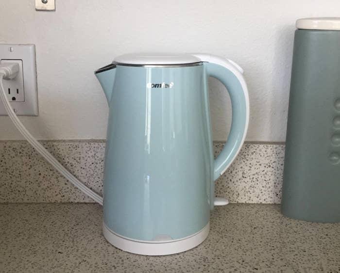 Mint green tea kettle on a kitchen counter