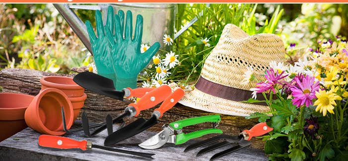Gardening tools with a pair of gloves and a hat.