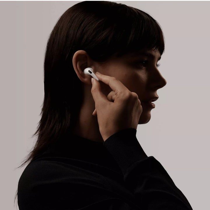 A model putting in a pair of white Apple Airpod Pro headphones
