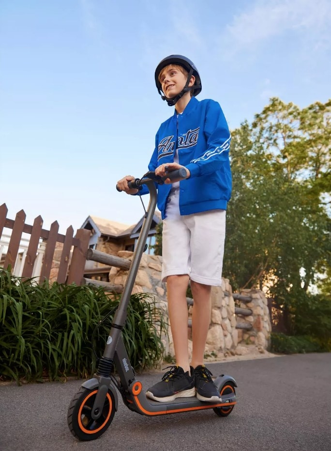 A model using theSegway Ninebot E12 Electric Scooter in black and orange