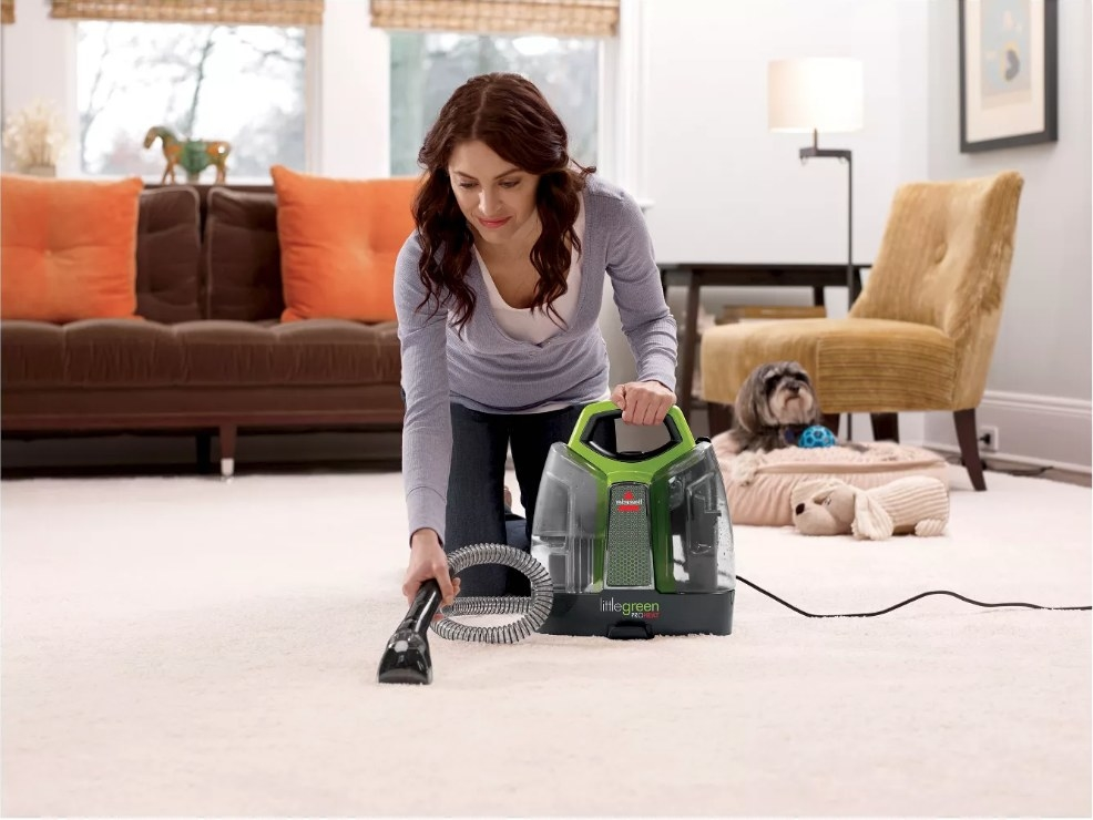 A model using the Bissell Proheat portable deep cleaner to remove a stain on a carpet
