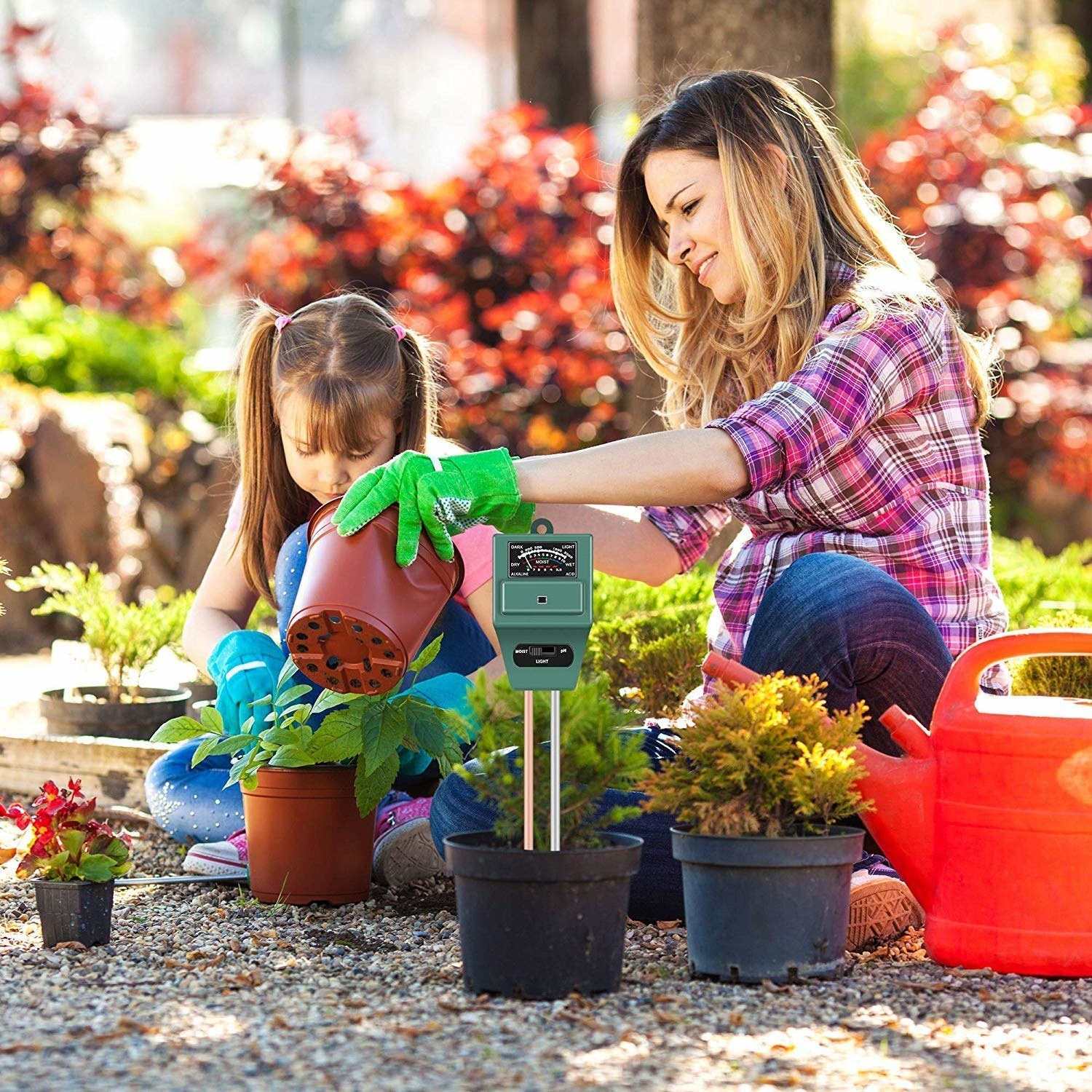 A women with a child who are planting pots and testing the soil with a sensor.