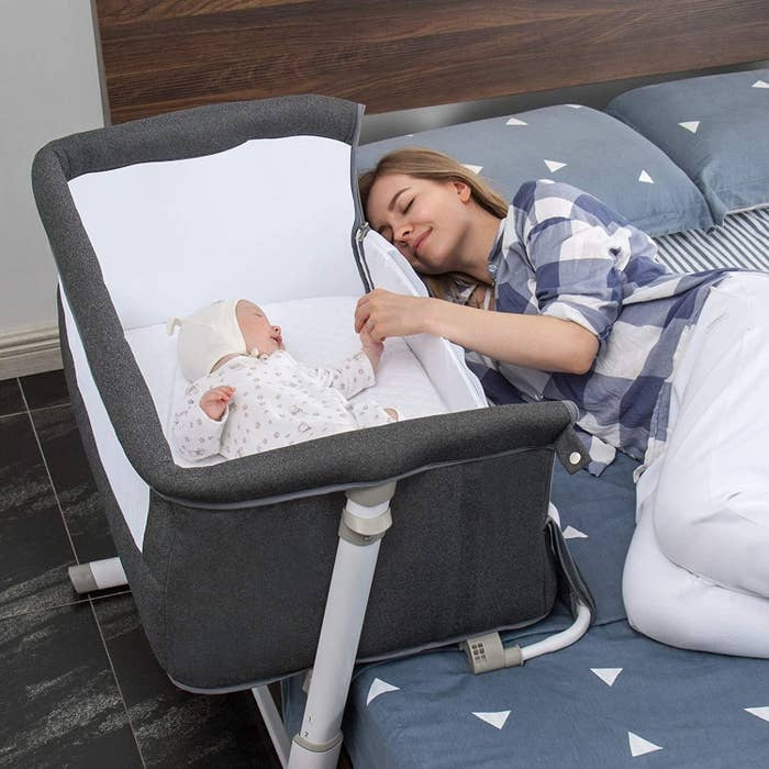 Parent in bed with baby in bassinet