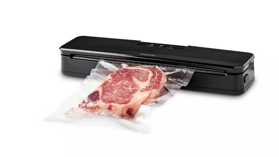 TheAnova Precision vacuum sealer in black sealing a raw piece of steak