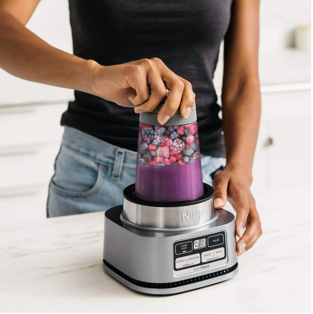 A model using theNinja Foodi Smoothie Bowl Maker and Nutrient Extractor/Blender to make a berry smoothie