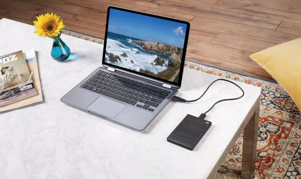 TheSeagate 2TB external hard drive in black plugged into a laptop
