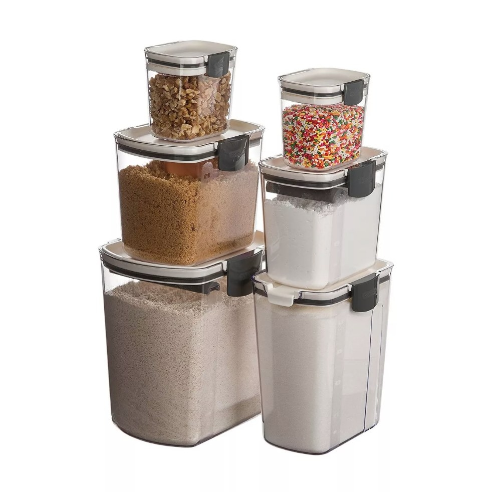 A 6-piece, clear, airtight food storage canister set filled with flours, sugars, sprinkles, nuts, and more