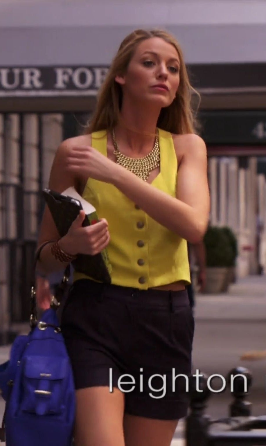 Serena in a sleeveless button up vest with high waisted shorts and a big chain necklace