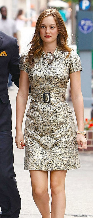 Blair in a metallic floral print short sleeve collared sheath short dress with big pockets on the skirt, a thick matching belt, and a metal flower at the collar