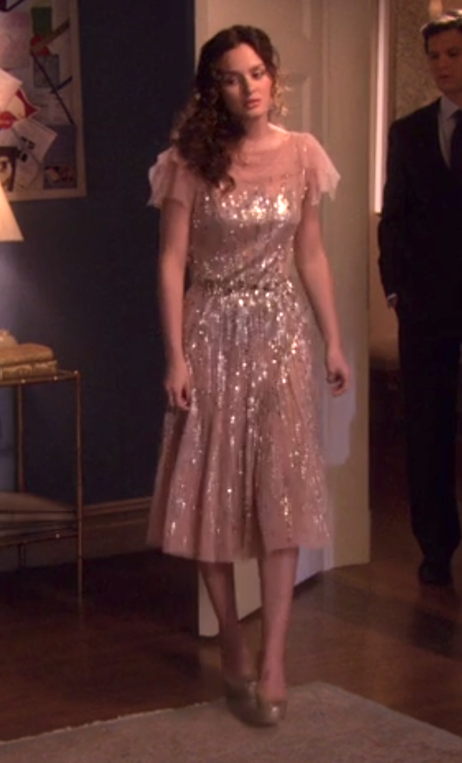 Blair in a flutter short sleeve high neck sheer dress that goes down to her knees with sequins all over and a sparkly thin belt