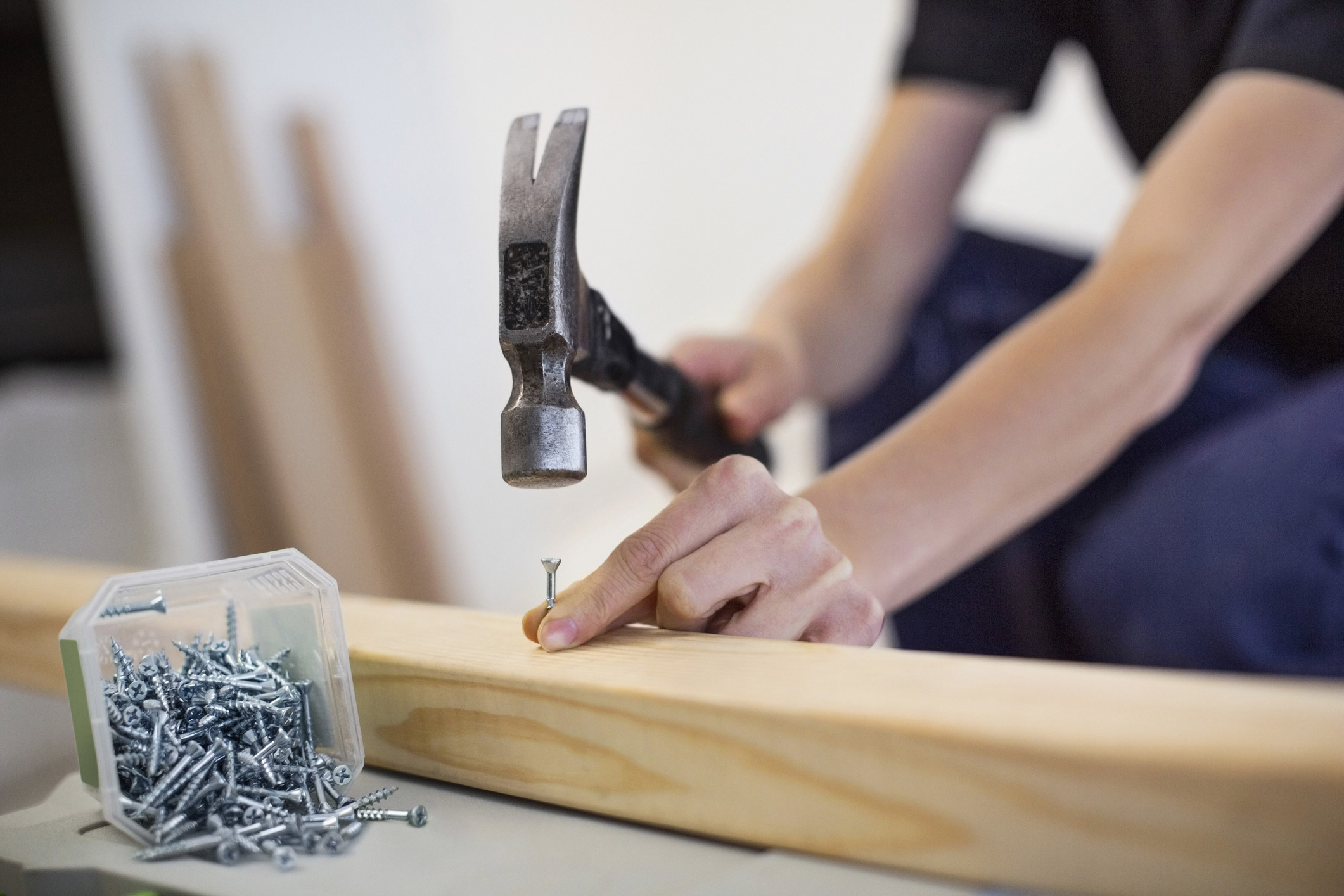 a person hammering a nail into a beam