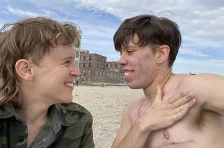 Two trans people smile at each other at Riis Beach, NYC