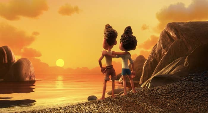 Two friends with their arms around each other's shoulders as they look at the sun