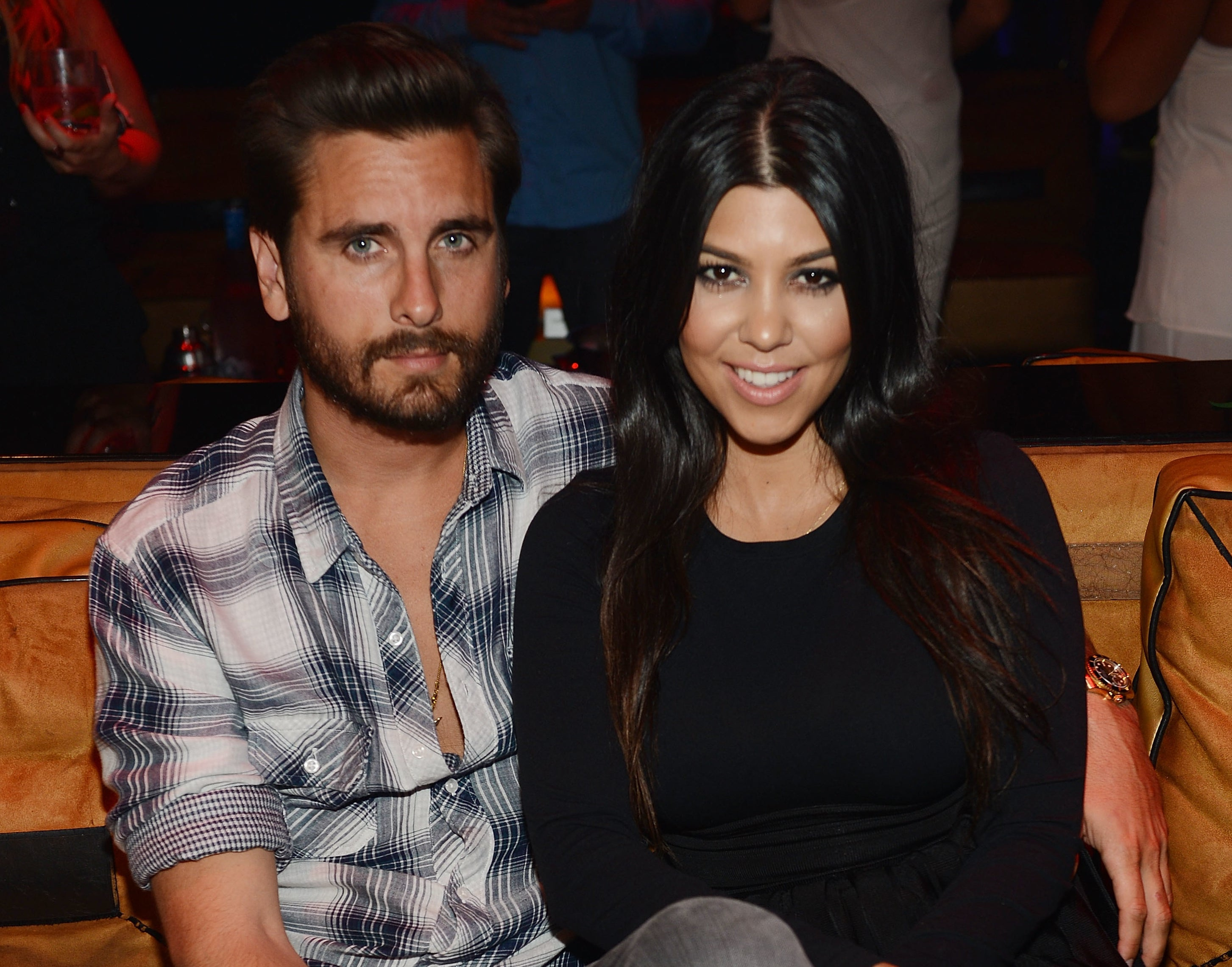 Scott and Kourtney smile while sitting next to each other in an old photo