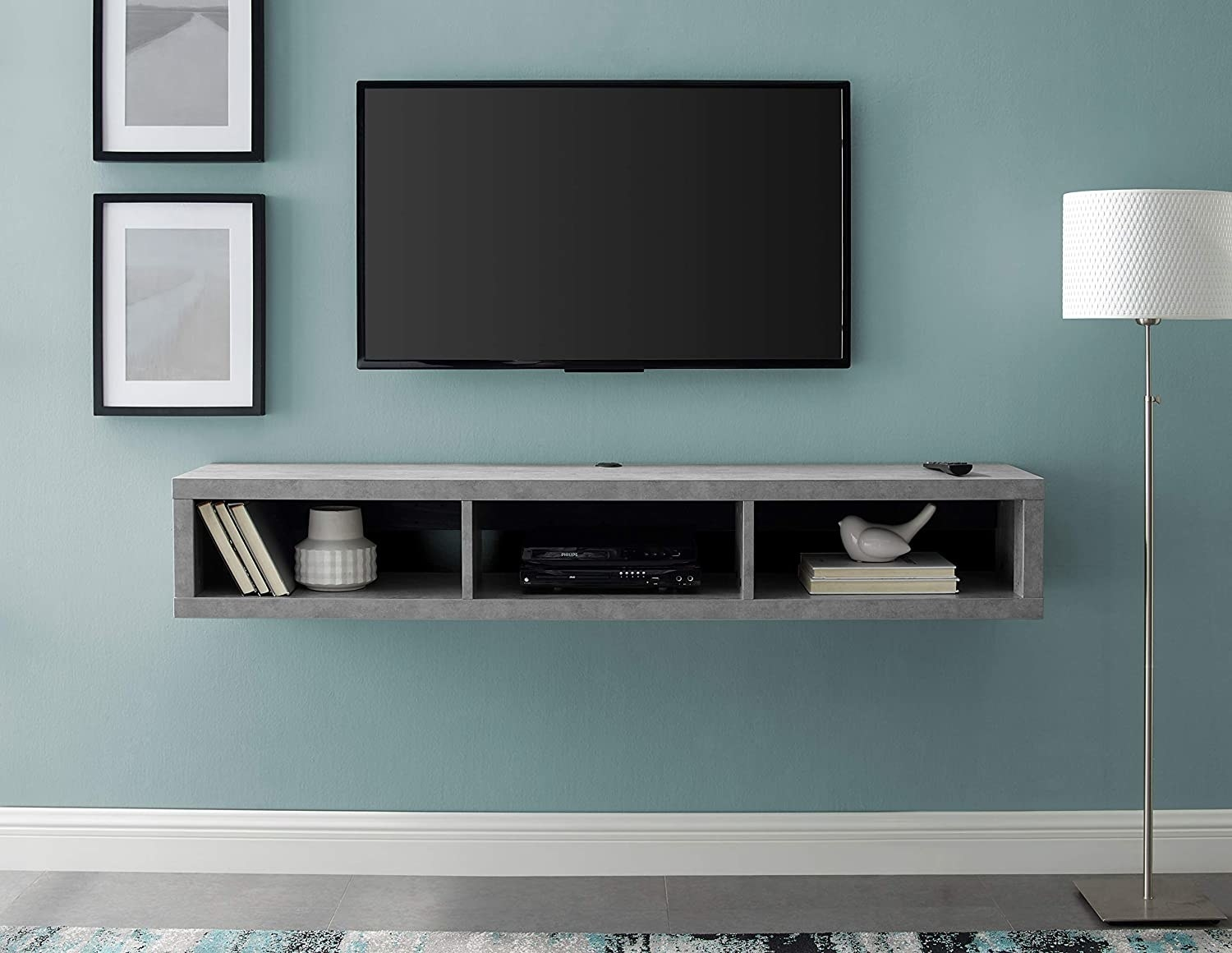 Gray floating TV console under TV mounted on wall