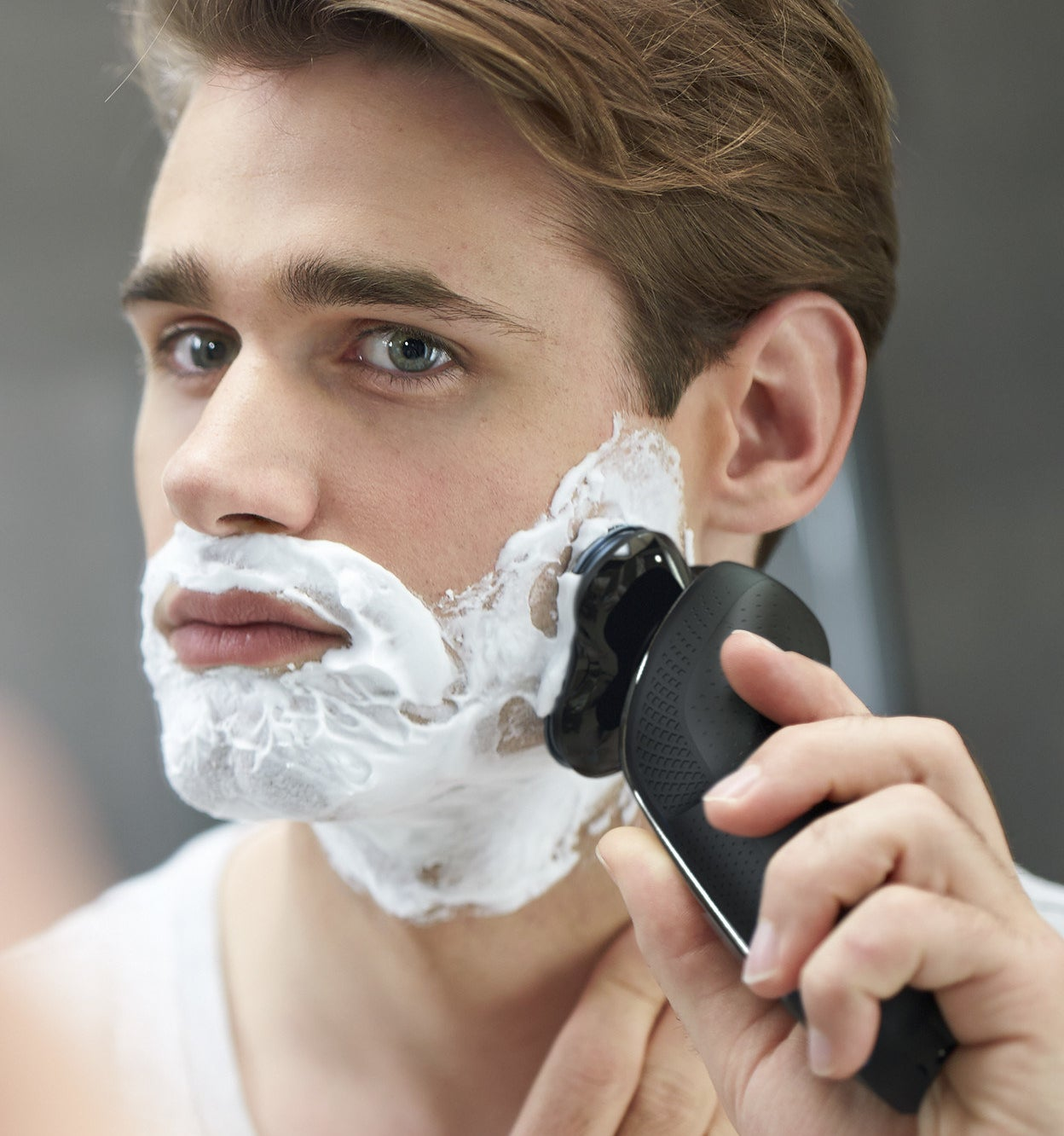 A model uses the product with shaving cream on their face demonstrating that this can be used for wet shaving