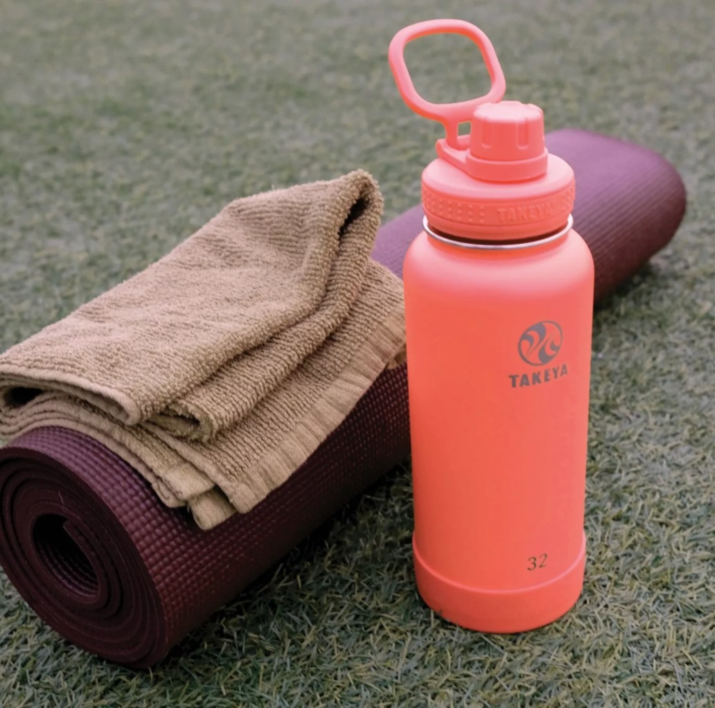 The water bottle in the color coral next to a yoga mat