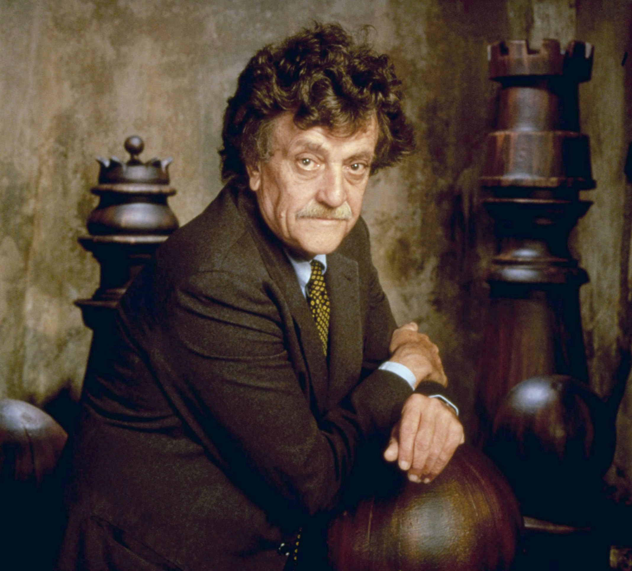 Kurt Vonnegut in a suit and polka dot tie posing with giant chess pieces