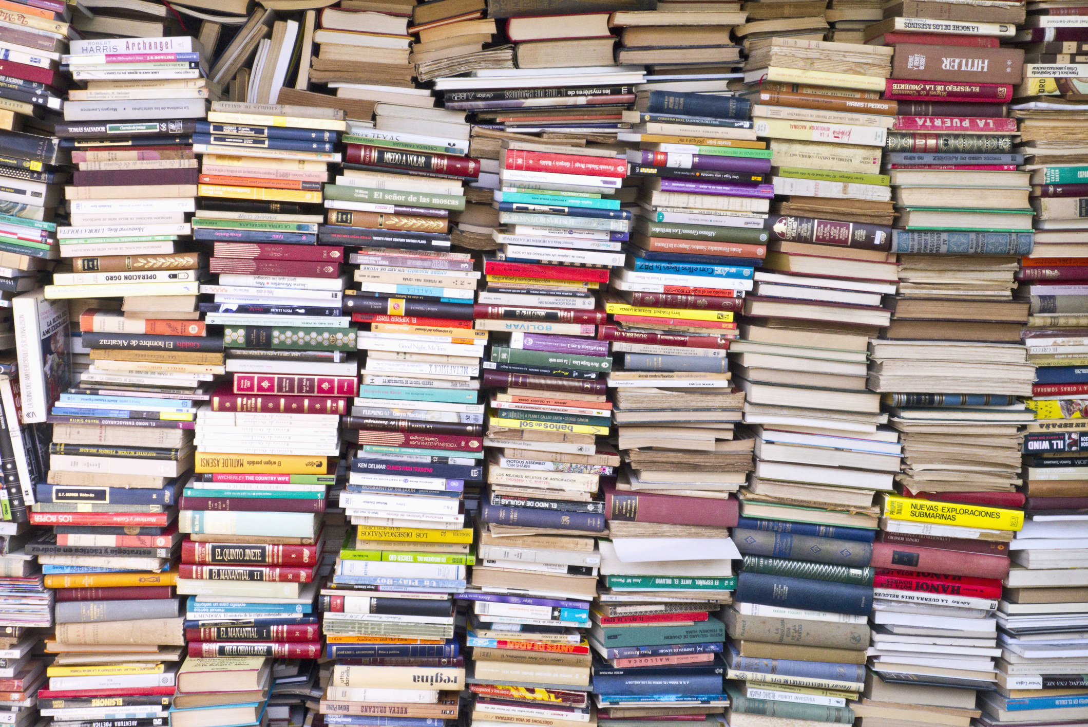 Tons of books in stacks, some spine out and some page-side out