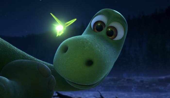 Spot the dinosaur looks at a firefly flying by at night, a sense of wonder in his eyes