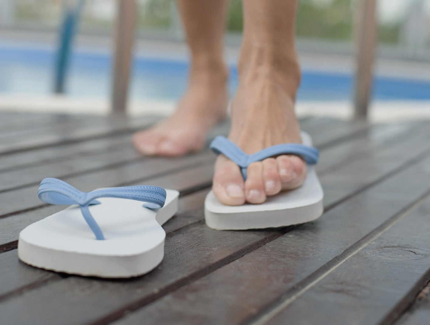 Someone stepping out of the pool, wearing one flip-flop